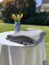 Load image into Gallery viewer, 100% Flax Linen Throw Charcoal and Natural with Ardmore pottery vase and spring tulips in country garden
