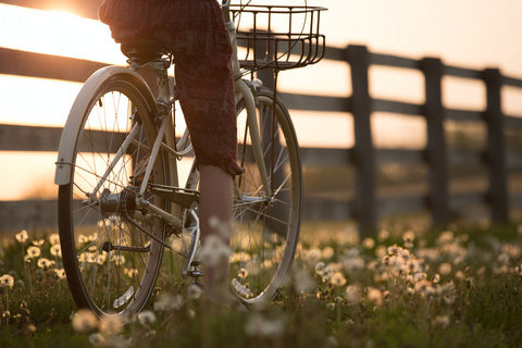 person rides bicycle along path at sunset