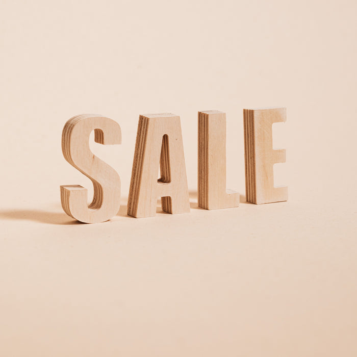 Image of the word sale in all caps, made out of wood, on a background of light beige.