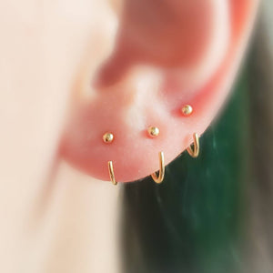 3 yellow gold open huggie hoops with 2mm ball beads on ear