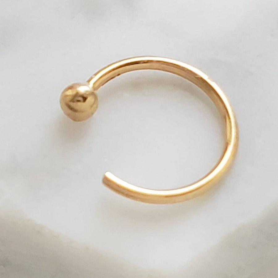 Yellow gold open hoop  with 2mm ball bead marked 14k  on white background