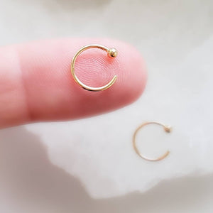 Yellow gold open hoops with 2mm ball beads one on index finger on white background