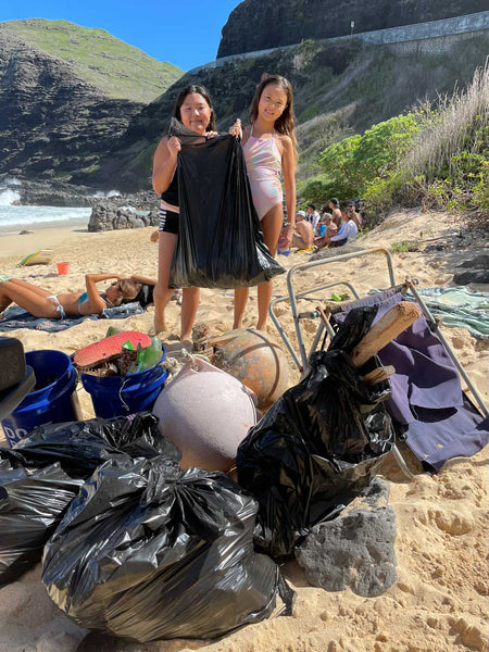 Two girls at the beach cleanup cleaning microplastics
