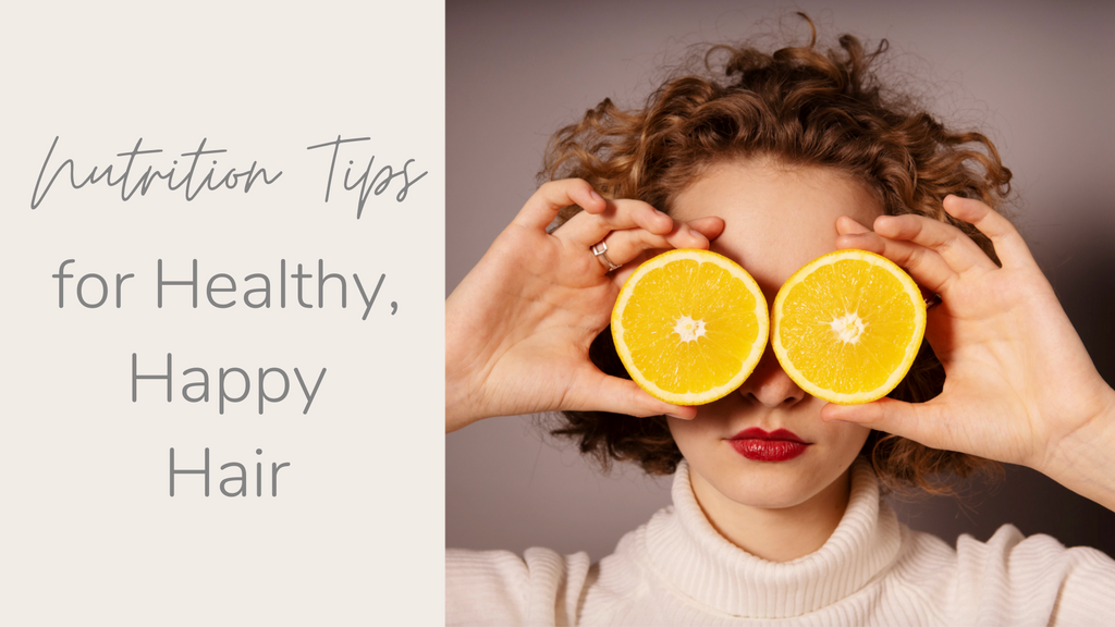 Text reads nutrition tips for healthy happy hair next a photo of a woman with curly hair holding lemon slices over her eyes