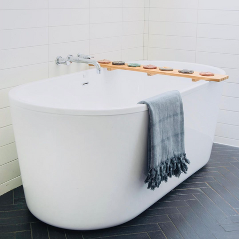 A grey stray & wander turkish towel hanging over the edge of a white bath tub in a white washroom