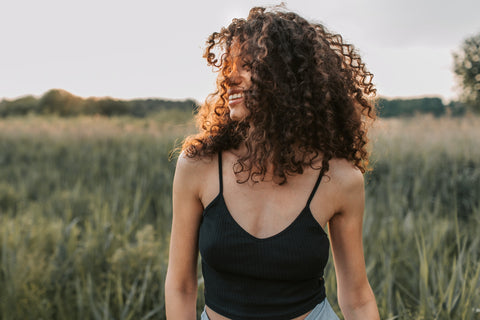 Woman with healthy curly brown hair smiling in a field