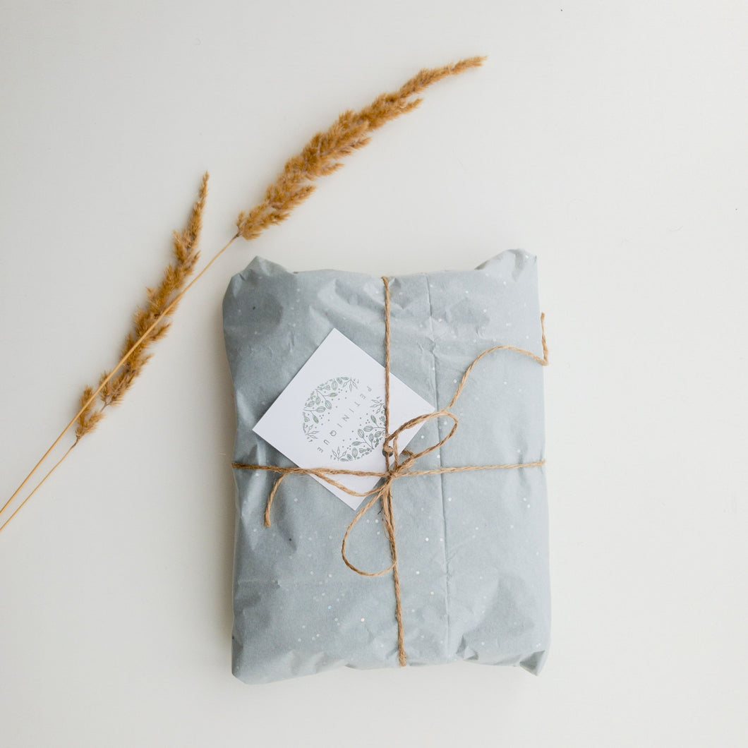 A picture of a gift wrapped in blue paper and tied with a natural string. There are two pieces of grass laying beside it.