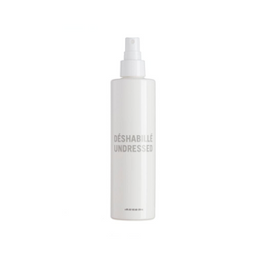"White bottle that reads ""Undressed"" in grey - it's a non-toxic natural texturizing finishing spray from Hairstory for sexy beachy waves"