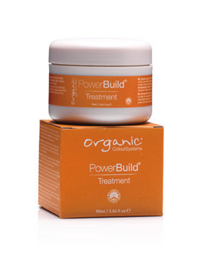 Orange box that reads Organic Colour Systems PowerBuild Treatment with a white jar of the product on top of the box - ideal treatment for strengthening and nourishing hair naturally