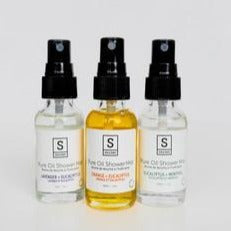 Image of three clear bottles with black lids. One has a light orange colour oil inside, the other two have clear oils - they read Souldeo Pure Oil Shower Mist, made with essential oils