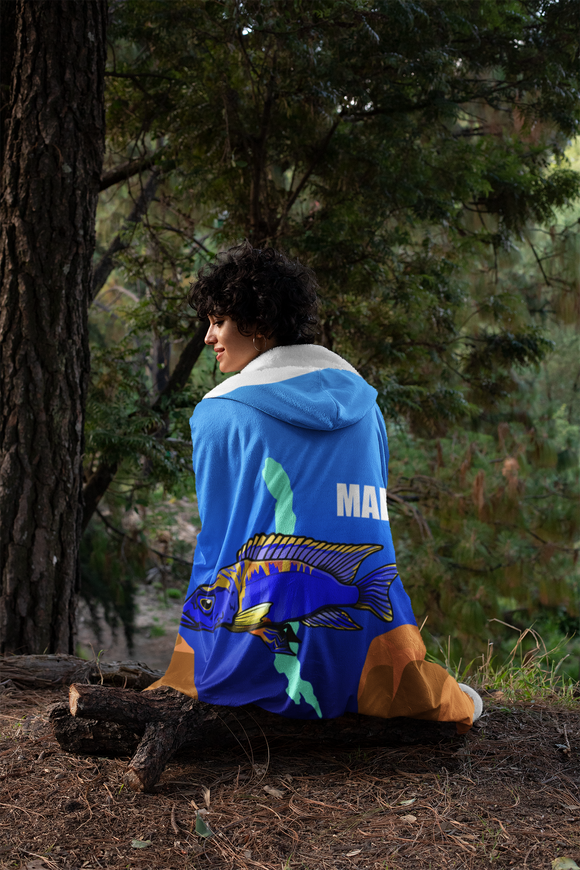 Aulonocara Lwanda Cichlid Lake Malawi Hooded Blanket shown worn on by a woman sitting on a log in the woods