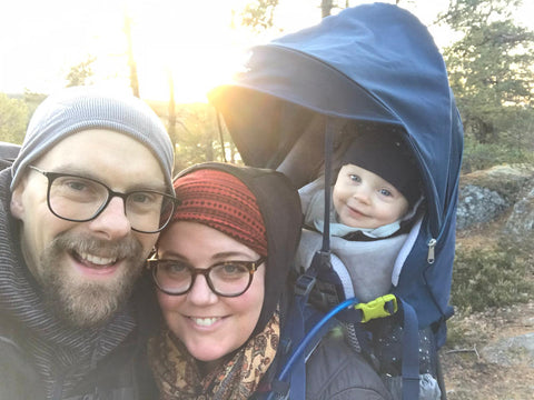 Family photo showing mom, dad and baby on a hike in nature.