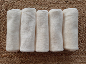 5 cloth wipes folded neatly and lying side by side on a natural fiber background.