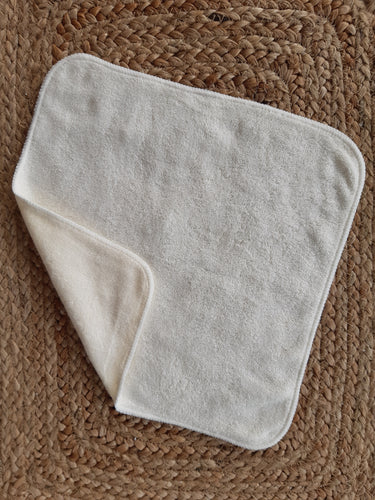 Photo of reusable cloth wipe on natural fiber background.