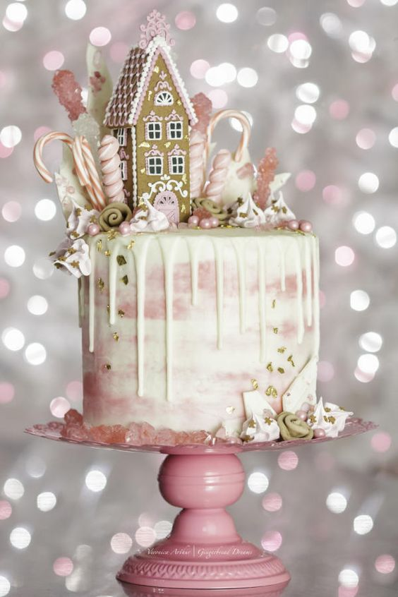 A pink drip cake with a gingerbread house topping.