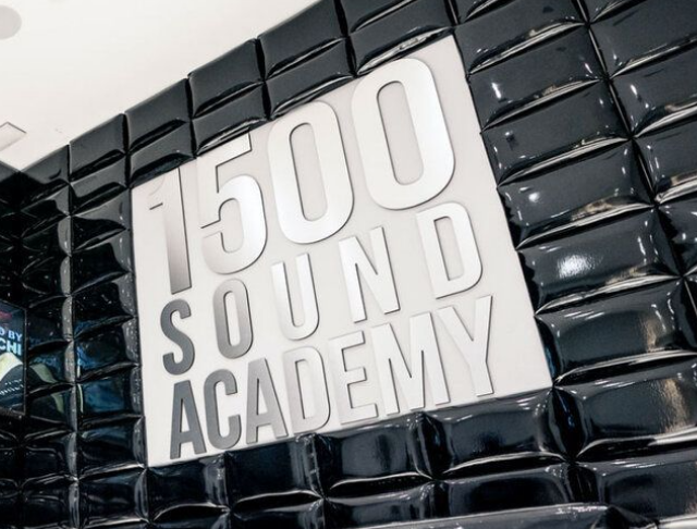 """a silver """"1500 Sound Academy"""" sign against a black background"""