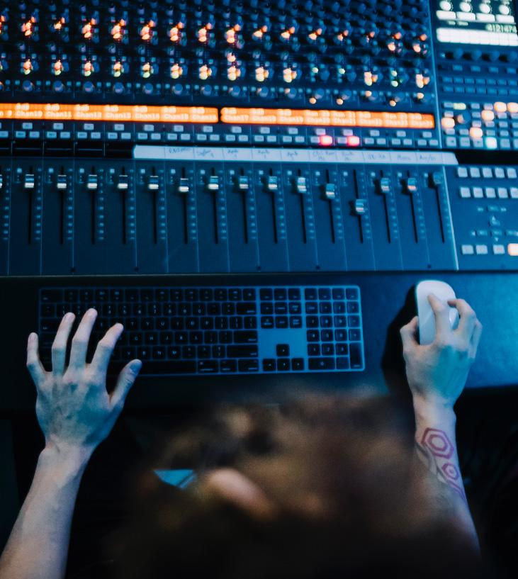 a person adjusting the settings on music production equipment