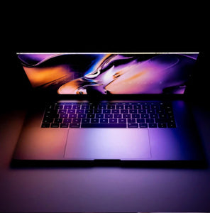 a laptop half-open with swirly purple and orange wallpaper