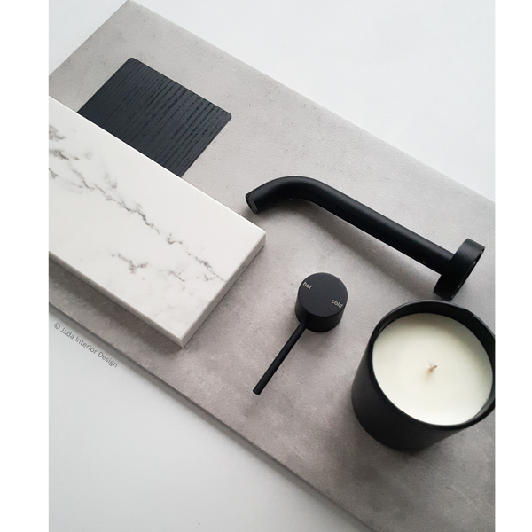 Moodboard with a large grey tile, with a small swatch of black laminate, a tile of white marble, black tapware and black candle with white wax