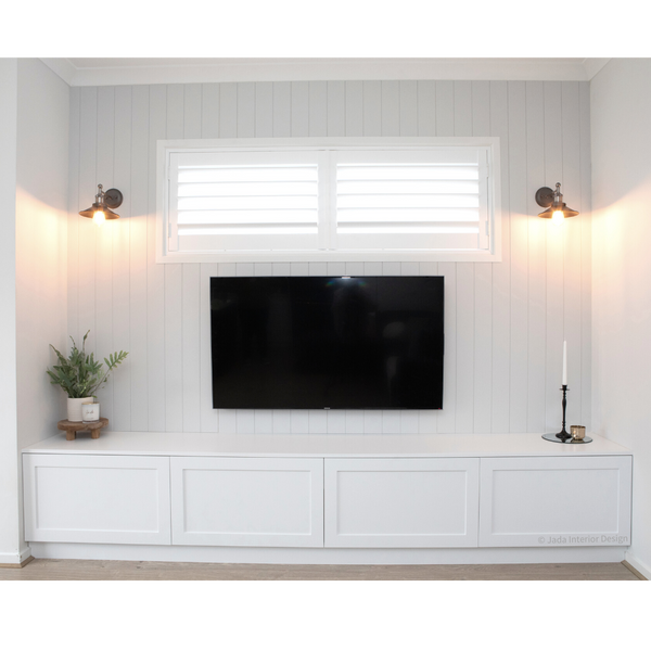 A white recessed area in the living area, with cabinetry along the bottom, tv in the middle attached to the wall, small rectangle window above the television with shutters, one vase on left side of the television, candlestick in holder to the right and black and gold sconces, turned on either side of the window.