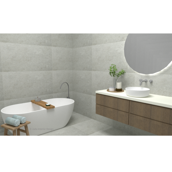 Computer render of a bathroom with large grey floor and wall tiles, white freestanding bath with a timber shelf caddy along the bath, a timber stool with 2 blue towels rolled on top, a floating timber vanity with white bench and white basin, a large round mirror on the wall above vanity and backlit with light, a small vase with branches.