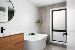 After photo of a bathroom that is now full of natural light, an almost floor to ceiling frosted window with a black frame, free standing bath, timber vanity and white top. Black hardware and a round mirror above the vanity