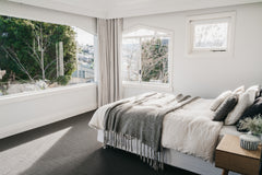 After photo of bedroom, light grey carpet, white walls, light grey sheer cutains, lots of natural light coming through windows opposite the bed which has white sheets,  and quilt and a grey throw at the end and grey pillows.