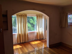 Before photo of dimly lit bedroom with a sectioned off smaller room, with an arch opening. brown walls, yellow flooring and beige curtains