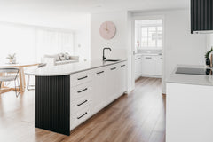 After photo of a living space that has been converted to a kitchen and walk in pantry. Timber flooring, black accents, white cabinetry and walls, black tapware