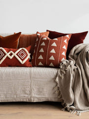 Beige linen couch, with burnt orange pillows with variousbeige patterns like diamonds and an oatmeal coloured linen throw hanging over the arm of the couch.