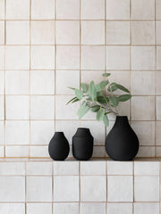 3 black ceramic, textured vases of various sizes and shapes, with the largest having a eucalyptus branch. All sitting a small tiled sill, against a wiled wall