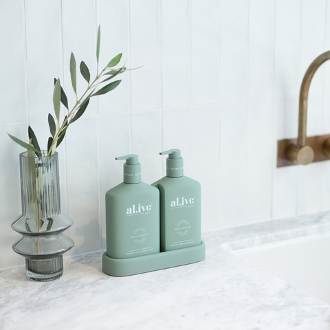 Alive Body Kaffir Lime & Green Tea Wash and Lotion Duo next to a vase with green leaves both on a white marble bathroom bench next to a sink and brass hardware