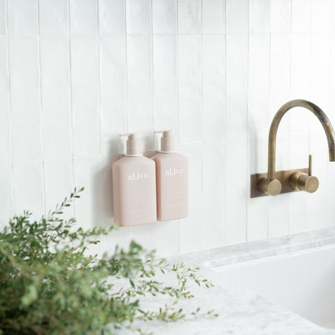 Alive Body Applewood and Goji Berry Body Wash and Lotion Duo together attached to the bathroom wall, white tiled splashback and white marble bench and sink, brass hardware and a green fern