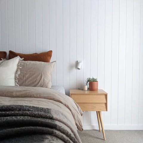 Half Bed, with beige quilt, matching pillow, white pillow and a burnt red pillow, and a dark, warm grey throw at the end of the bed. A timber bedside side table with thin, angled legs, a small terracotta pot plant, a white scone above the table and white panelled feature wall.