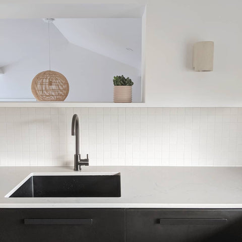 Close up of a newly renovated kitchen, a black undermount sink and matching black tapware, black cabinetry down below and a white benchtop. a white tiled backsplash.