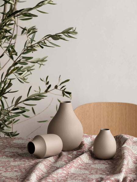 Latte coloured trio of vases, of various sizes and shapes, grouped together atop a dining table covered with a messily placed patterned reddish brown table cloth, the top of a timber dining chair and partial view of an olive tree as a centrepiece on the dining table