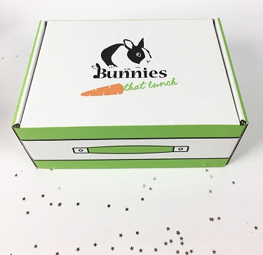Picture of branded cardboard box with star-shaped glitter around it.
