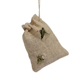 A small jute bag with a drawstring and two small holes cut in the side, alloiwing side, allowing hay to peek out.