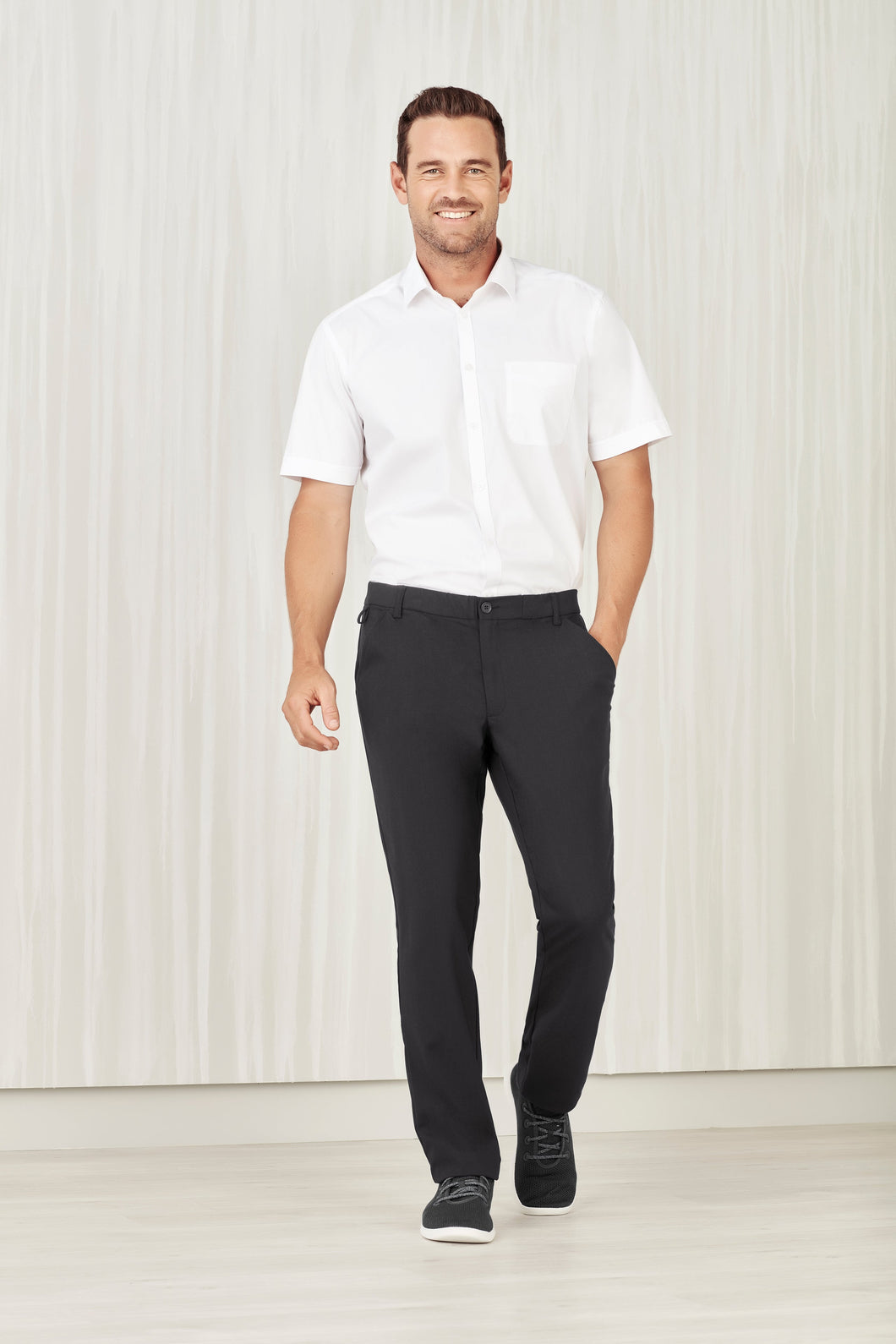 Man wearing charcoal comfort waist flat front pants