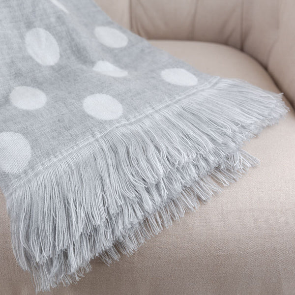 soft grey and white polka dot blanket with tassels