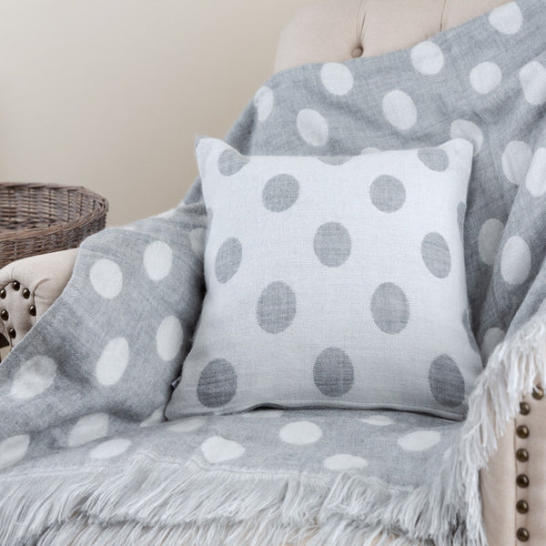 grey and white polka dot blanket and cushion on chair