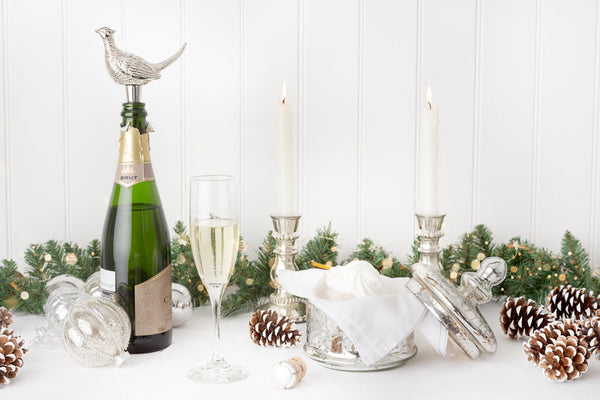 Decorated Christmas table with garland and champagne with a pheasant bottle stopper