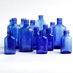 "A collection of cobalt blue milk of magnesia bottles in three sizes, each moulded ""Milk of magnesia registered trade mark"".  Rescued from a Victorian bottle dump, they have been cleaned and scrubbed, and their wonderful cobalt blue colour brought back to life."