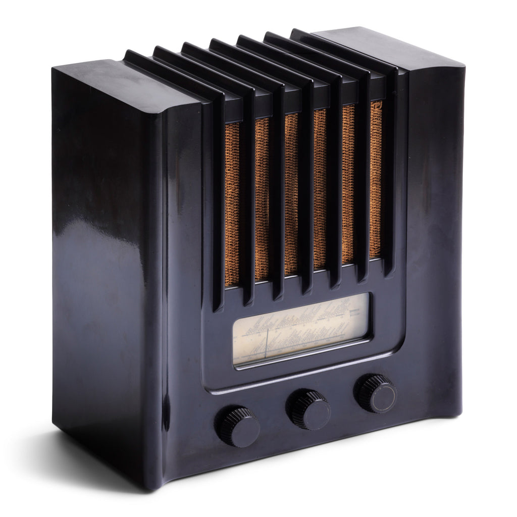 The British Murphy 4 valve AD 94  radio with distinctive Art Deco black Bakelite cabinet was manufactured from 1940.  Looking like a modernist building, this pioneering architectural style  radio resembles a powerhouse of electronic communications. Its streamline, futuristic mirrors  the Machine Age of the late 1930s.. Designed by Eden Minns in 1940.