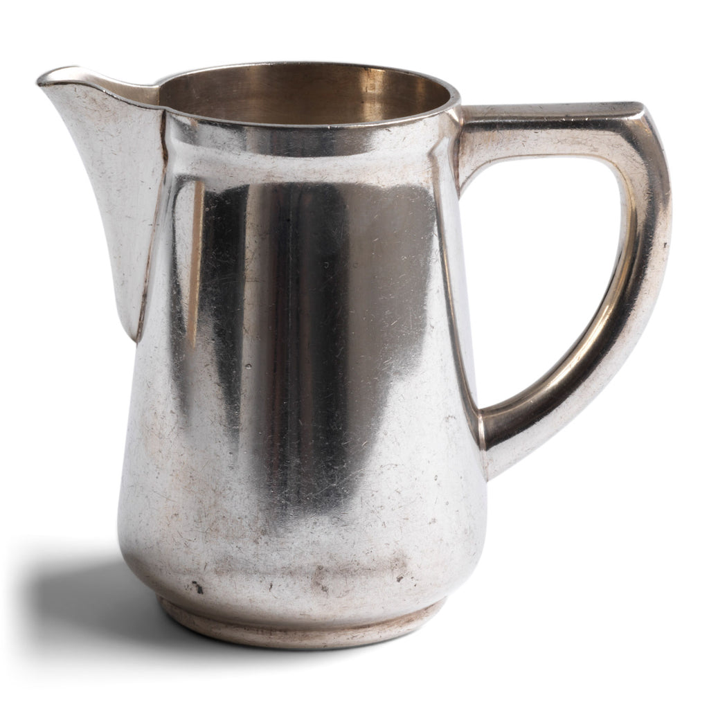 "A good, heavy-duty German WMF silver plated milk jug stamped ""Wurtt Metall W Fabrik"", an abreviation for Württembergische Metallwarenfabrik ( Württemberg metal factory), and ""Geislingen Steig"", the southern German town where the factory was based.  It also bears an arrow mark, indicating it was for military use - and was most probably made for an English officer's mess."