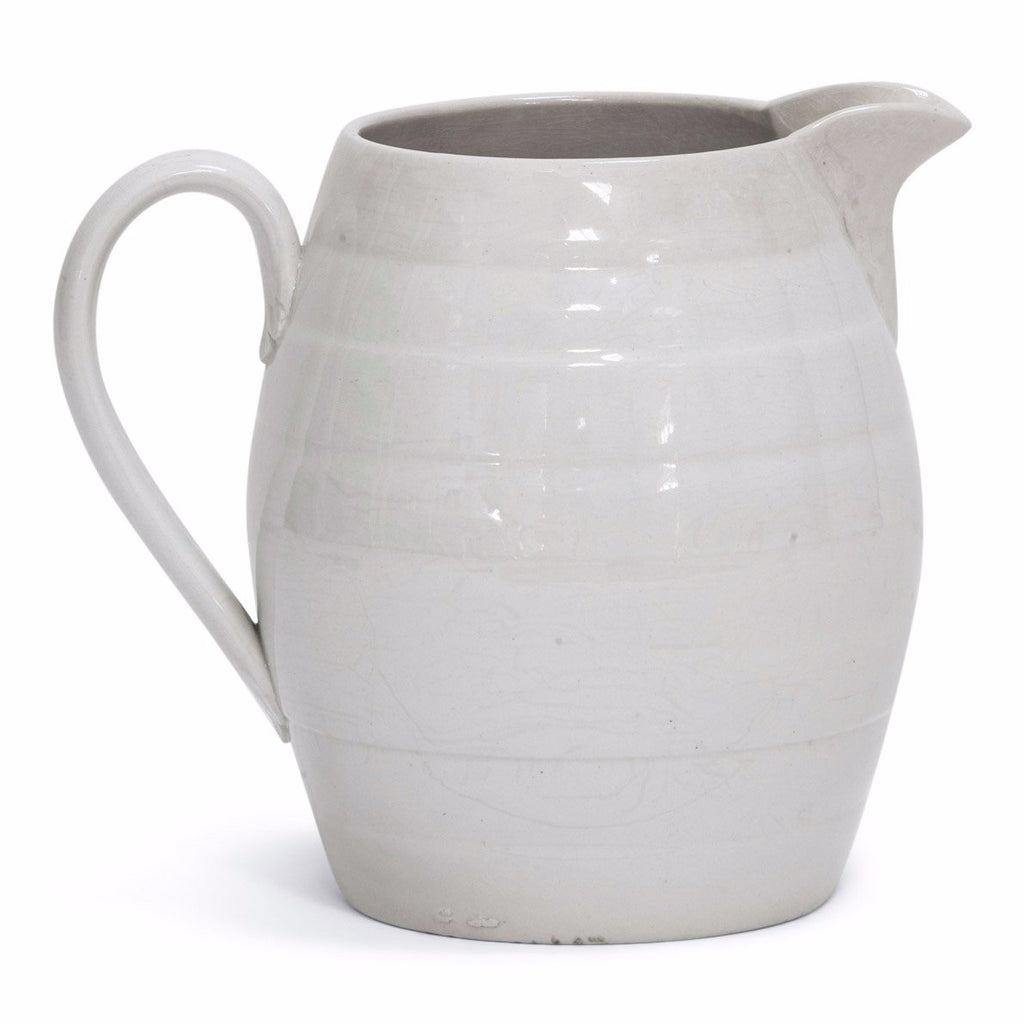 A 1920s barrel-shaped creamware water jug. Plain, unadorned water jugs with clean-lines and simple forms were part of the everyday 19th and early 20th century kitchen. Their purity and functionality is as appealing today as it was then; and when used for either water, milk or flowers, or simply amassed as a decorative collection, they make an arresting addition to the modern home.