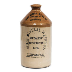"A handsome 1930s flagon with strap handle and bold utilitarian typeface: ""Edale Mineral Water Co Brewed Ginger Beer 1935 9a Edale Rd Rotherhithe S.E.16 - it is illegal to detain or use this jar for any other purpose, please return when empty""."