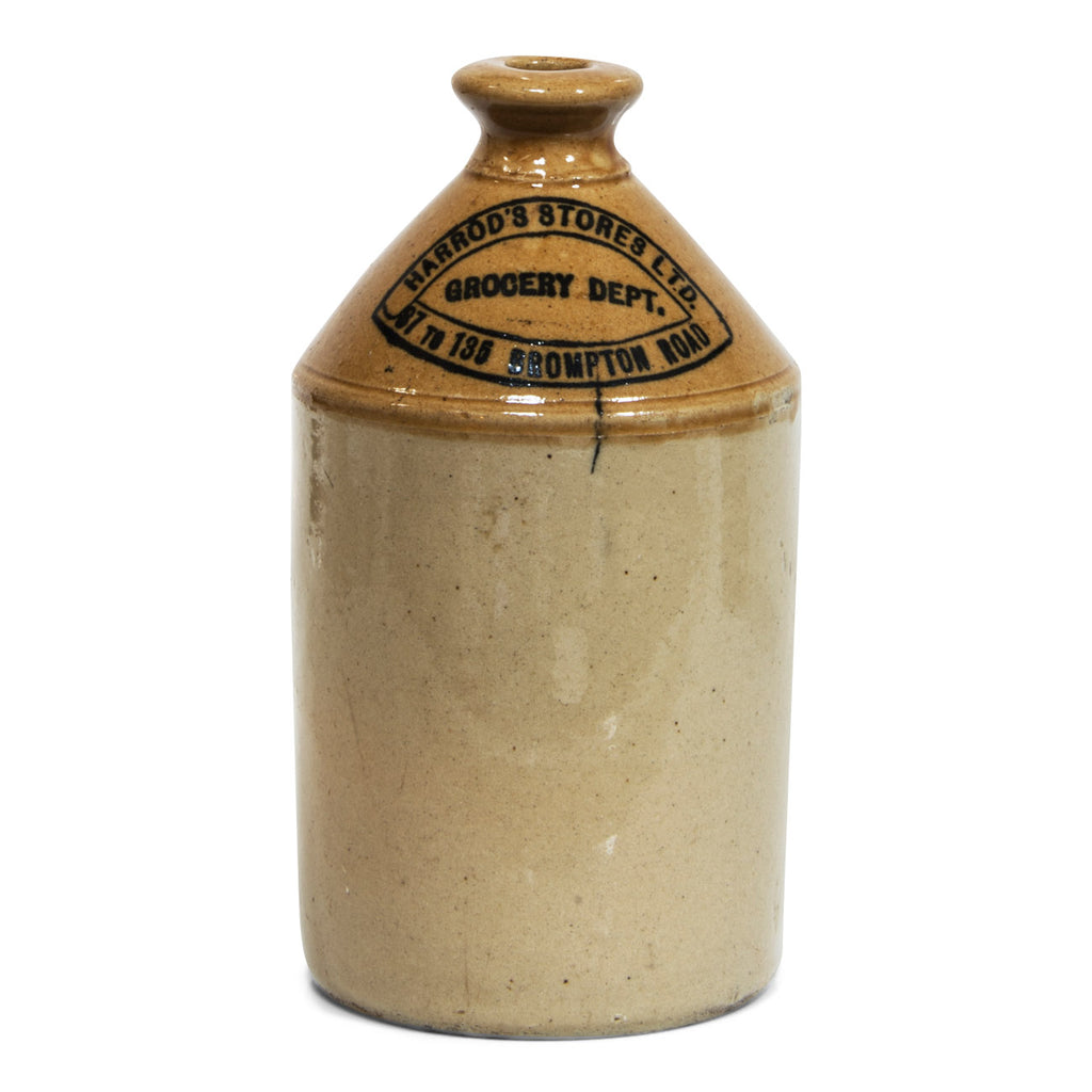 "A Victorian Harrods department store flagon with strap handle and bold nineteenth century typeface: ""Harrod's Stores Ltd Grocery Dept 87 to 135 Brompton Rd""."