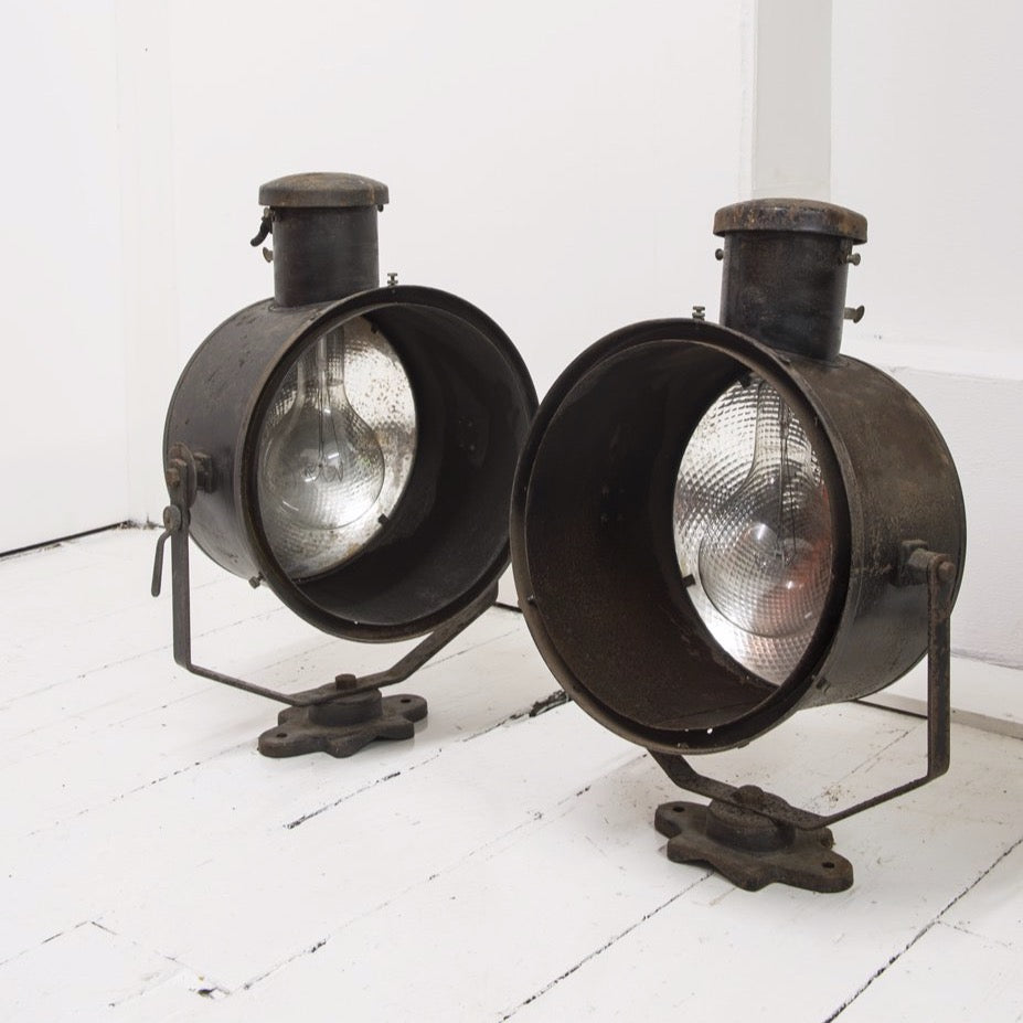 An impressive pair of early twentieth century stage lights, fitted with mercury glass reflectors, and with their original paint finish. Each light's steel housing swivels on a half-octagonal arm that is fitted with a bracket, affording the lights to be either wall or floor mounted. A side lever locks the lamp's desired angle in place.