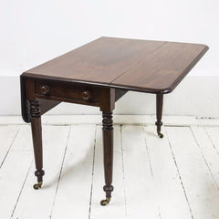 An elegant high quality solid mahogany Regency Pembroke table with single drawer on four faceted and turned legs, set on castors. A very handy and compact piece of furniture for the smaller home.  When part extended it can be used as a desk or for supper for two; fully extended it can seat several people for dinner; and when fully collapsed it can act as a hall or side table.